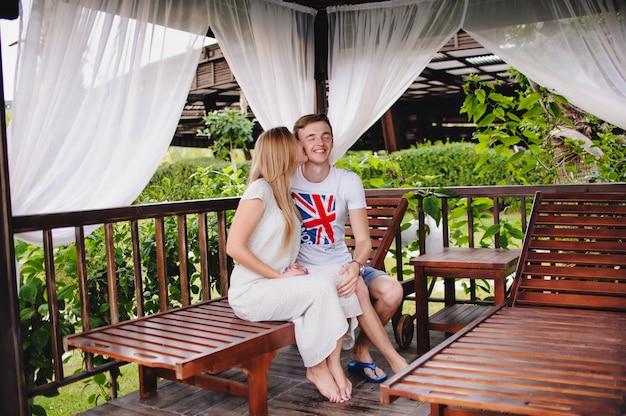 Heureux jeune couple s'embrassant dans un gazebo dans la nature