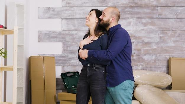 Heureux jeune couple s'embrassant dans leur nouvel appartement. boîtes en carton en arrière-plan.
