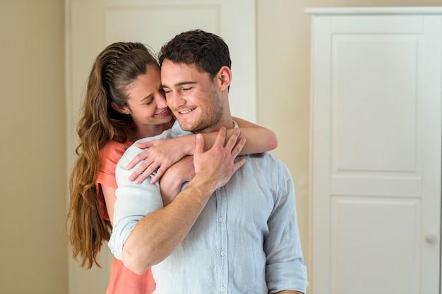 Heureux jeune couple s'embrassant dans le salon