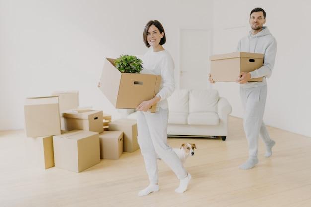 Heureux jeune couple s'installe dans la nouvelle maison, acheter de l'immobilier, occupé à transporter des effets personnels dans des boîtes en carton