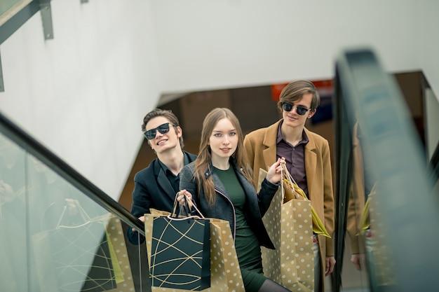 Heureux, jeune couple, à, sacs provisions, descendre, par, escalator, et, pointage doigt, dans, centre commercial