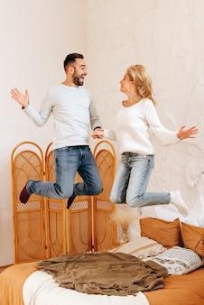 Heureux jeune couple sautant sur le lit. gai, espiègle, les jeunes s'amusent dans la chambre