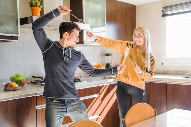 Heureux jeune couple se battre avec une spatule et un fouet