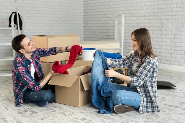 Heureux jeune couple se déplaçant dans de nouvelles boîtes de déballage maison, s'amuser