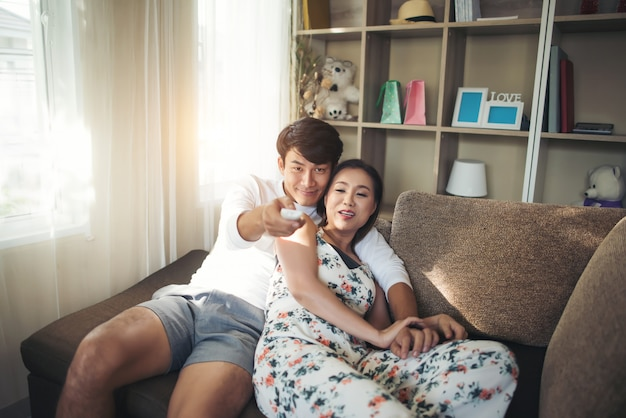 Heureux jeune couple se détendre et regarder la télévision au salon