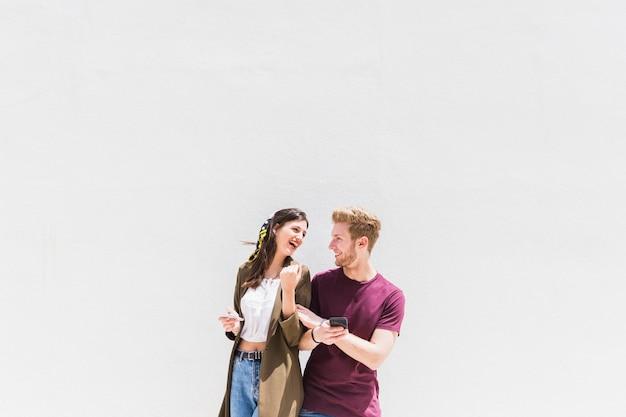 Heureux jeune couple avec smartphone debout sur fond blanc