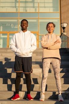 Heureux jeune couple sportif interculturel en vêtements de sport debout contre l'escalier et l'architecture moderne en milieu urbain