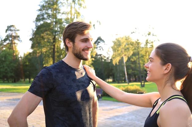 Heureux jeune couple sportif parlant en se tenant debout dans le parc.