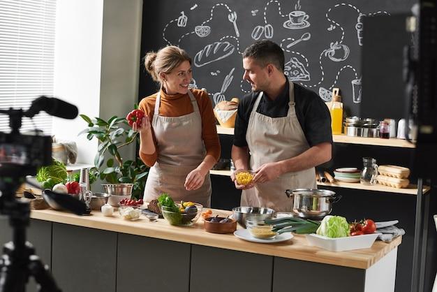 Heureux jeune couple en tabliers debout dans la cuisine et discutant de la nouvelle recette ensemble, ils tirent le blog