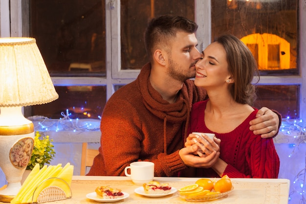 Heureux jeune couple avec des tasses de thé
