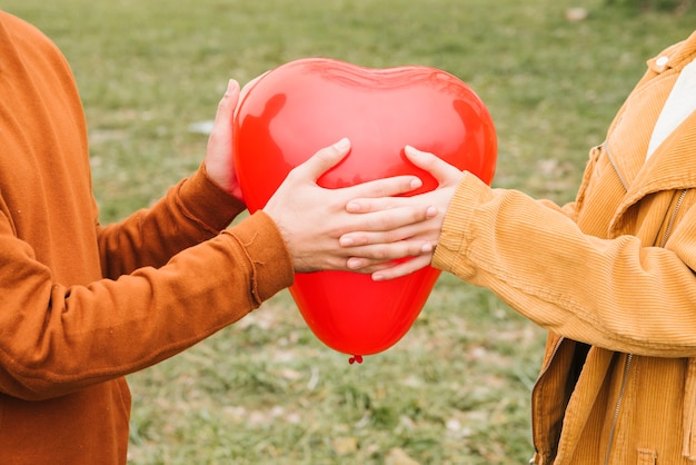 Heureux jeune couple tenant un ballon en forme de coeur