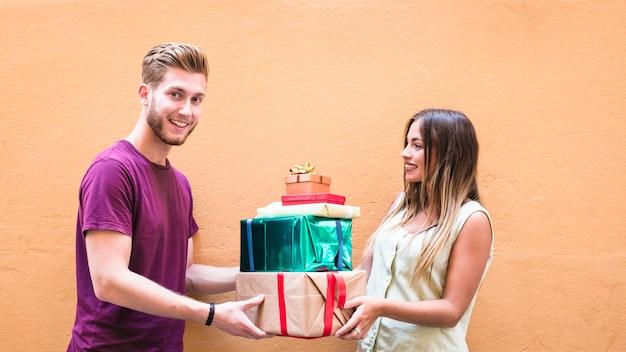 Heureux jeune couple tenant la pile de cadeaux sur fond orange