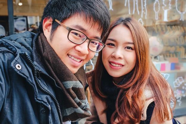 Heureux jeune couple de touristes asiatiques prenant un selfie dans la ville