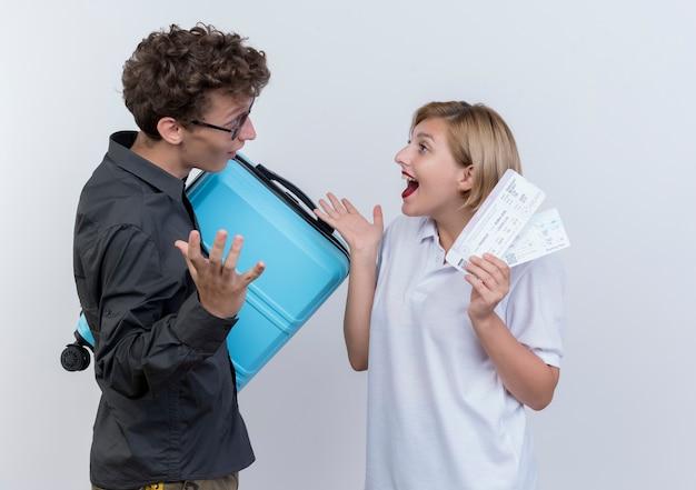 Heureux jeune couple de touristes surpris homme tenant valise en regardant sa petite amie heureuse avec des billets d'avion en mains debout sur un mur blanc