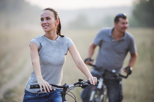 Heureux jeune couple avec des vélos dans la campagne.