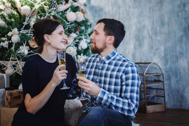 Heureux jeune couple avec des verres de champagne à la main, arbre de noël en arrière-plan.