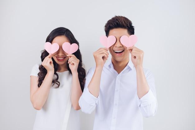 Heureux jeune couple vietnamien tient des coeurs en papier rose et souriant