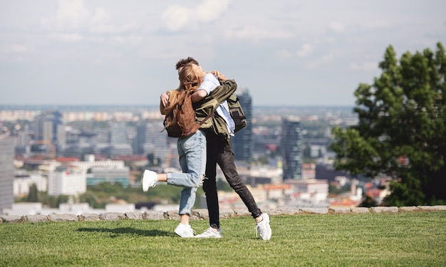 Heureux jeune couple voyageurs en ville en vacances, s'embrassant. paysage urbain en arrière-plan.