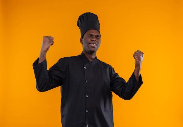 Heureux jeune cuisinier afro-américain en uniforme de chef se lève les poings avec les yeux fermés sur orange avec copie espace