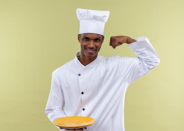 Heureux jeune cuisinier afro-américain en uniforme de chef tient la plaque et lève le poing isolé sur mur vert