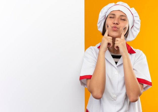 Heureux jeune cuisinier en uniforme de chef debout devant un mur blanc en mettant les doigts sur les joues avec les yeux fermés isolés sur le mur orange
