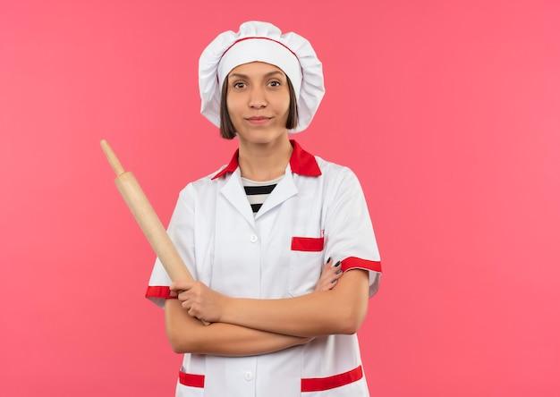Heureux jeune cuisinier en uniforme de chef debout avec une posture fermée et tenant un rouleau à pâtisserie isolé sur un mur rose