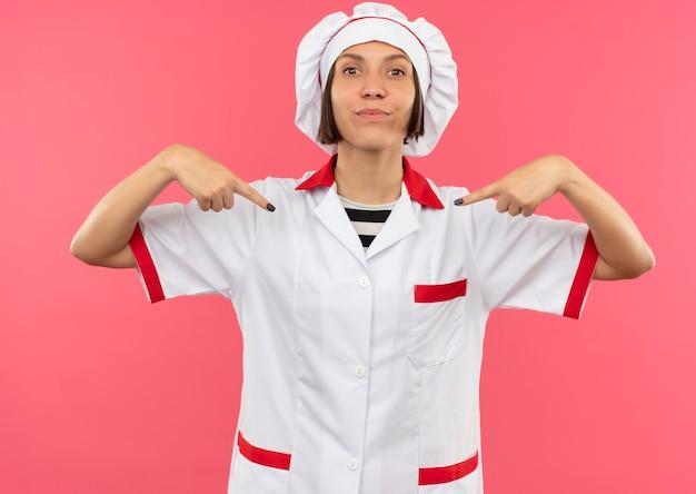 Heureux jeune cuisinier en uniforme de chef pointant sur elle-même isolé sur un mur rose