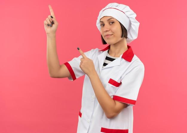 Heureux jeune cuisinier en uniforme de chef pointant vers le haut isolé sur mur rose