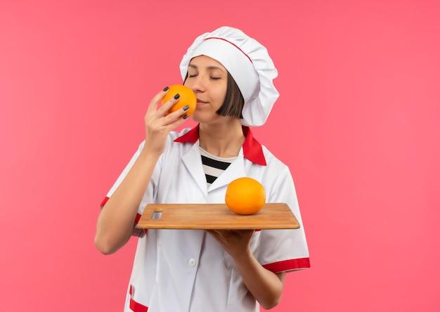 Heureux jeune cuisinier en uniforme de chef tenant une planche à découper avec orange dessus et reniflant l'orange avec les yeux fermés isolé sur mur rose