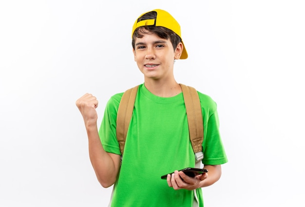 Heureux jeune écolier portant un sac à dos avec une casquette tenant un téléphone montrant un geste oui isolé sur un mur blanc