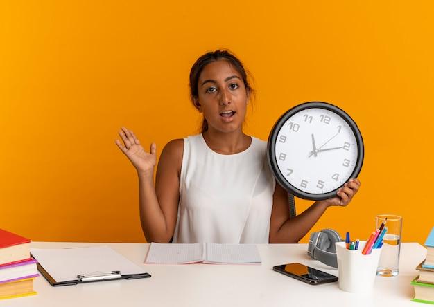 Heureux jeune écolière assis au bureau avec des outils scolaires tenant une horloge murale et répandre la main sur l'orange