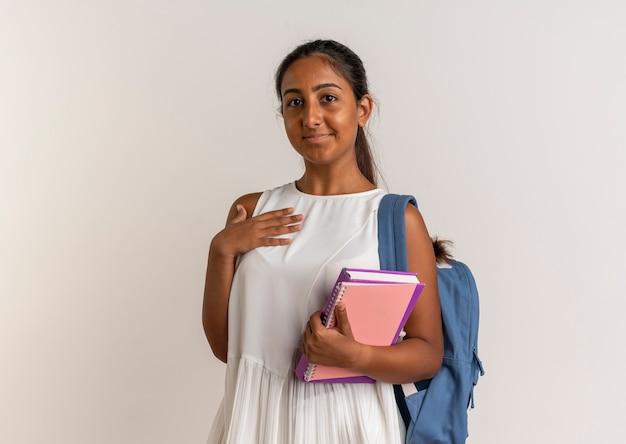 Heureux jeune écolière portant sac à dos tenant le cahier et les points avec la main sur elle-même sur blanc