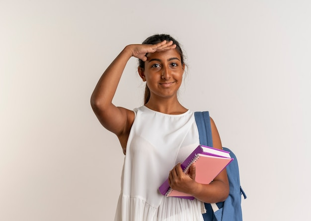 Heureux jeune écolière portant sac à dos tenant le cahier et regardant à distance avec la main sur blanc