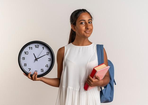 Heureux jeune écolière portant sac à dos tenant livre avec horloge murale isolé sur blanc