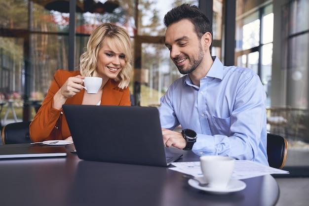 Heureux jeune employé de bureau aux cheveux noirs montrant quelque chose sur l'ordinateur portable à sa patronne souriante