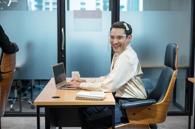 Heureux jeune employé de bureau travesti asiatique travaillant avec ordinateur portable et document au bureau au bureau