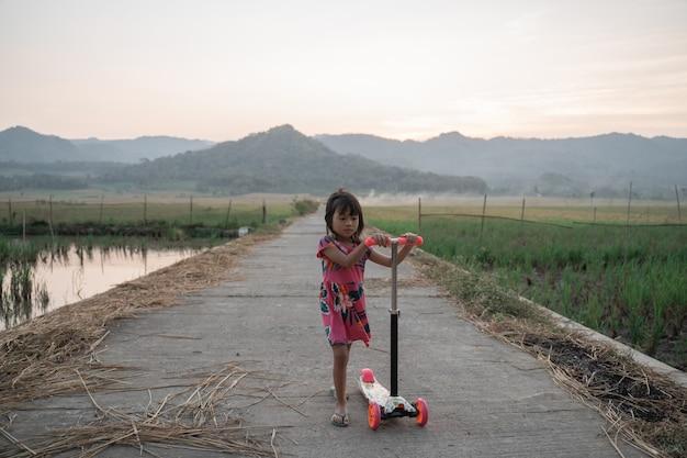 Heureux jeune enfant monter son scooter en plein air