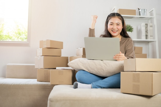 Heureux jeune entrepreneur asiatique, sourire pour le succès des ventes après avoir vérifié la commande de la boutique en ligne