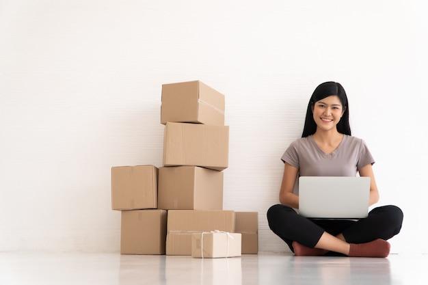 Heureux jeune entrepreneur asiatique sourire pour le succès des ventes après avoir vérifié la commande