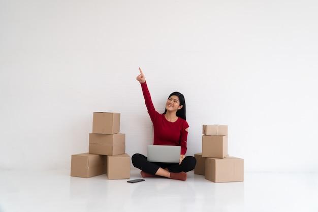 Heureux jeune entrepreneur asiatique, sourire pour le succès des ventes et pointer du doigt vers le haut au bureau à domicile