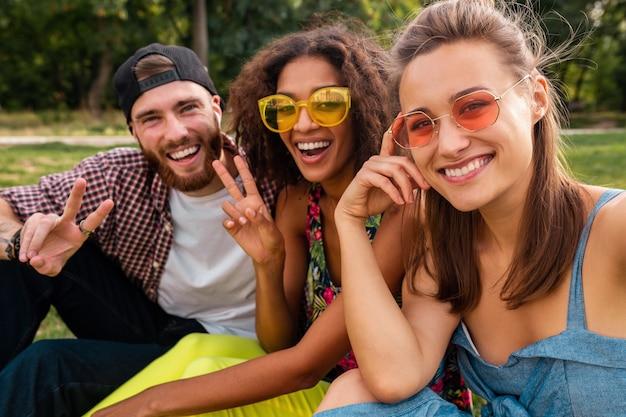 Heureux jeune entreprise élégante et colorée d'amis assis dans le parc, l'homme et la femme s'amusant ensemble
