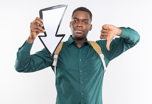 Heureux jeune étudiant afro-américain avec sac à dos tenant une flèche et pointant vers le bas isolé sur un mur blanc avec espace de copie