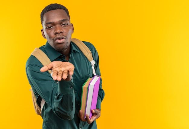 Heureux jeune étudiant afro-américain avec sac à dos tenant des livres et envoyant un baiser avec la main