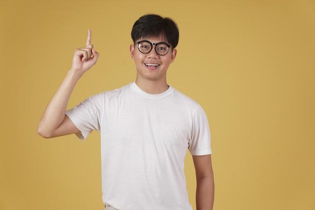 Heureux jeune étudiant asiatique joyeux habillé avec désinvolture portant des lunettes pointant le doigt vers le haut ayant idée isolée