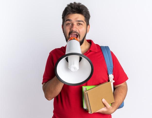 Heureux jeune étudiant barbu en polo rouge avec sac à dos tenant des cahiers criant au mégaphone debout