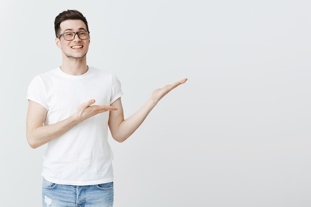 Heureux jeune étudiant pointant les mains à droite