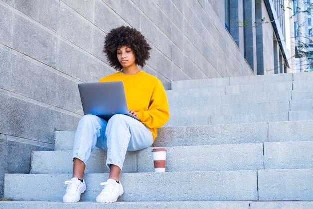 Heureux jeune étudiant travailleur africain femme d'affaires relaxant s'asseoir sur les escaliers de la ville. en regardant l'écran d'un ordinateur portable, regardez des vidéos en ligne de webinaires sur un ordinateur se reposant sur le lieu de travail, travail terminé