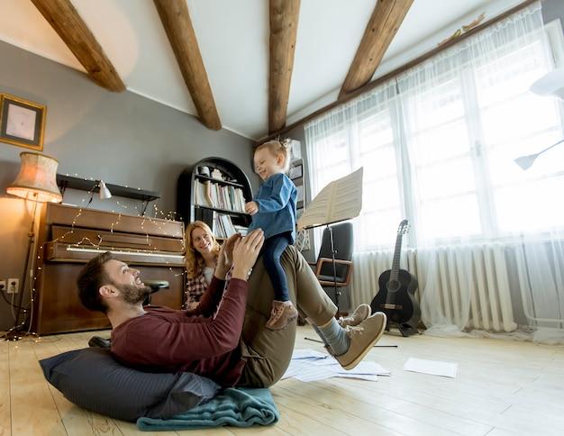 Heureux jeune famille jouant sur le sol dans une chambre rustique