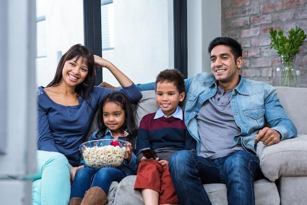Heureux jeune famille manger du maïs soufflé en regardant la télévision