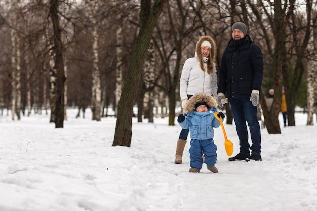 Heureux jeune famille marchant dans un parc d'hiver